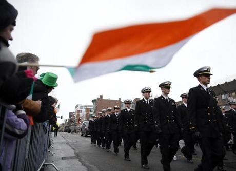 A person held an Irish flag as members of the Regimental Band and Honor Guard from Massachusetts Maritime Academy march during the 2015 St. Patrick's Day Parade in South Boston.